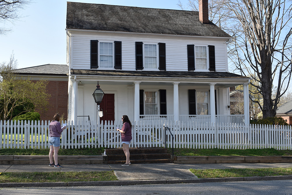 Emily Rider and Emalee Young stand outside the Utzman-Chambers House on S. Jackson Street to discuss the answer.